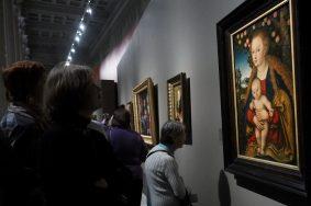 """Посетители у картины  Лукаса Кранаха Старшего """"Мадонна с младенцем под яблоней"""" около 1530. Выставка в ГМИИ им.Пушкина""""Кранахи. Между ренессансом и маньеризмом""""."""