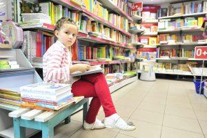 """Подростки выбирают книги из школьной программы перед началом учебного года. Книжный магазин """"Москва"""". На снимке Анита Моралова."""
