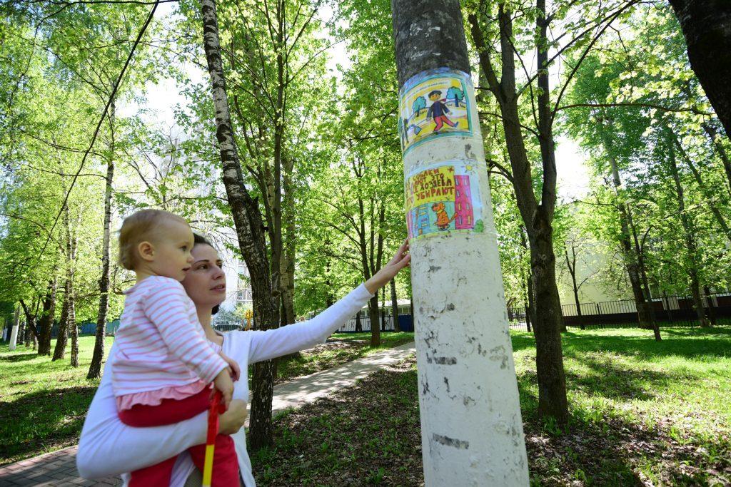 8 мая 2018 года. Жительница района Северное Чертаново Елена Головина показывает своей дочери рисунок, обращенный к владельцам собак. Фото: Пелагия Замятина