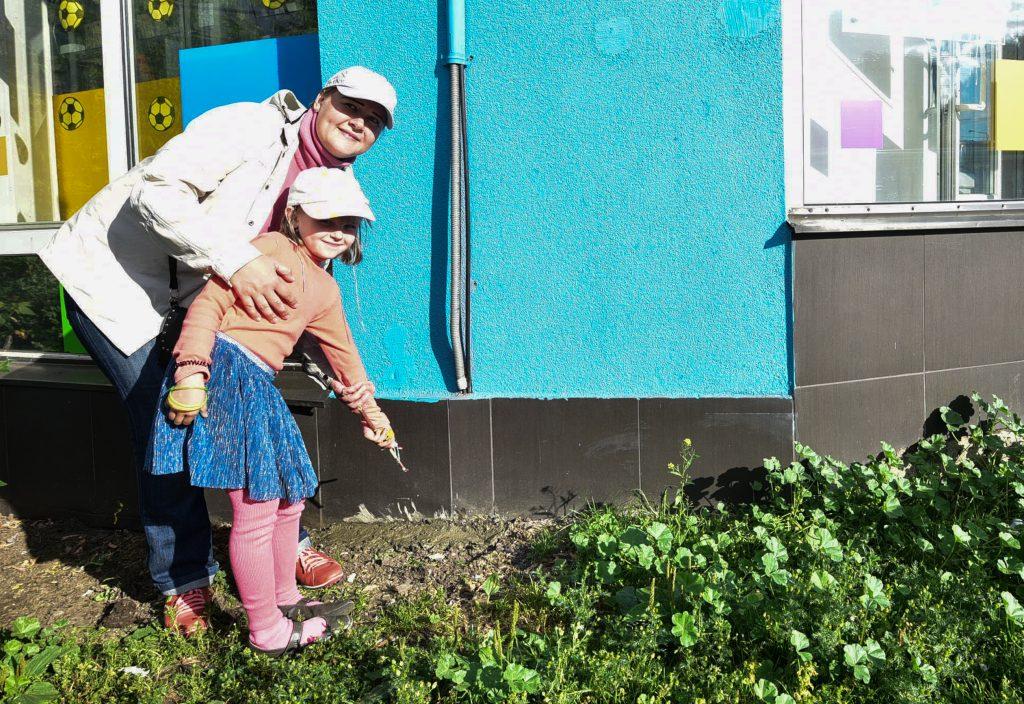 6 июля 2018 года. Екатерина Тихонова с дочкой Елизаветой показывают место, где под торговым павильоном раньше были норки грызунов. Теперь они все замурованы. Фото: Пелагия Замятина