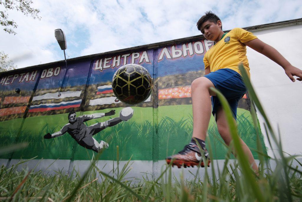 9 июля 2018 года. Юный футболист Аким Сулейманов тренируется на фоне граффити в честь Игоря Акинфеева. Фото: Максим Аносов