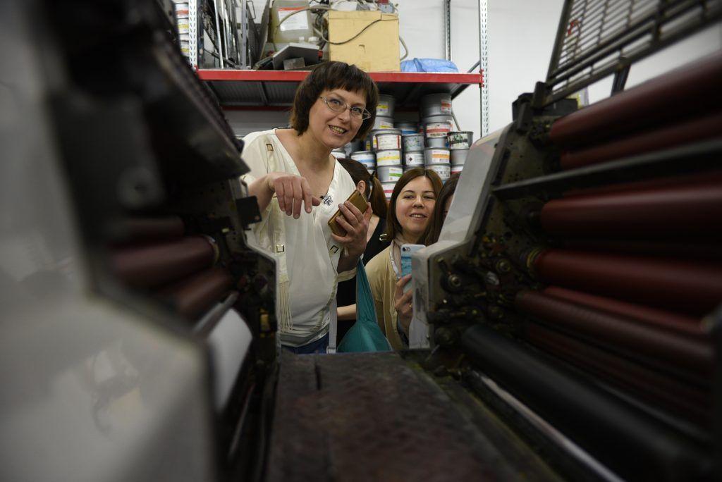 Мастер Юрий Цись показывает Екатерине Аникиной и Марине Гладковой, как работает станок офсетной печати. Фото: Пелагия Замятина