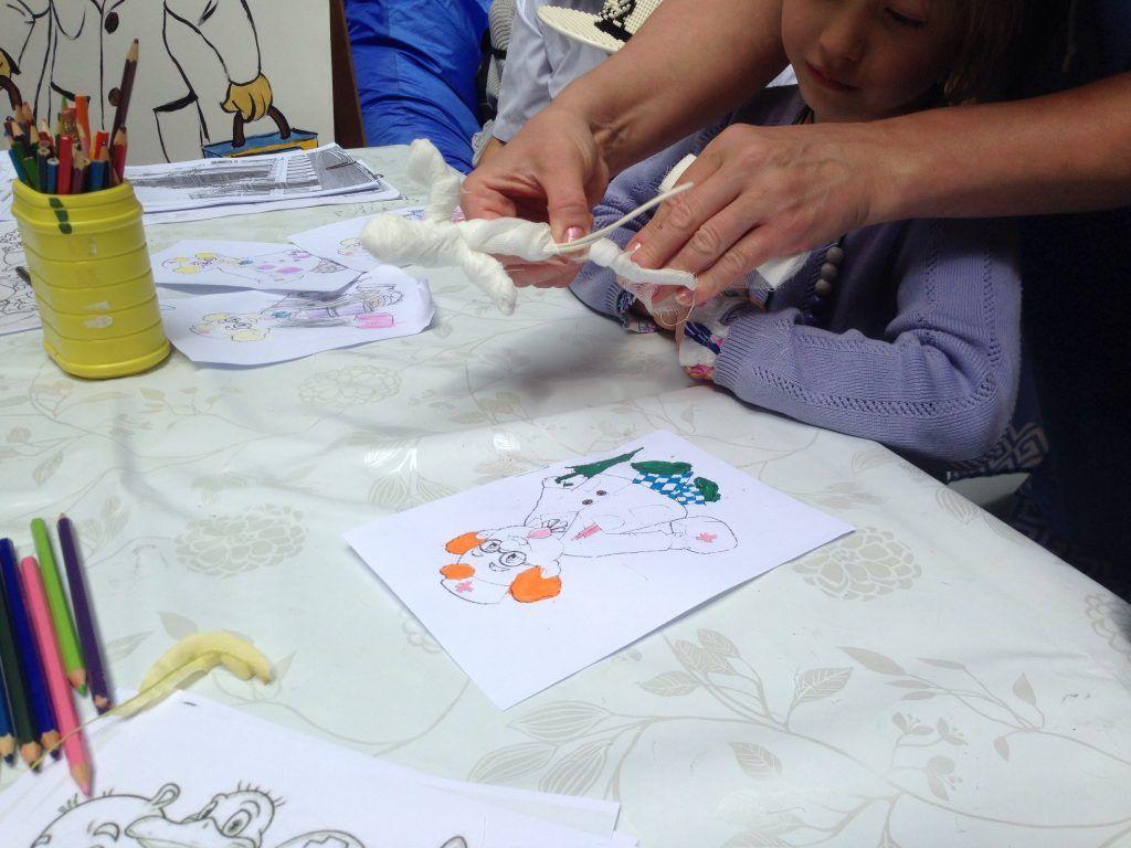 Сотрудница библиотеки показывает детям, как смастерить куклу. Фото: Виктория Чуранова